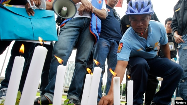 FILE - A local policeman offers flowers to the victims of the Manila bus hostage crisis in 2010 at the Luneta Park in Manila on August 23, 2013.