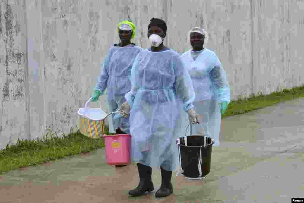 لائبیریا کے دارالحکومت میں ایبولا سے متعلق نئے تشخیصی مرکز کے اہلکار وہاں سامان لے کر جا رہے ہیں۔