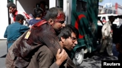 An Afghan man carries an injured man to a hospital after a blast in Kabul, Afghanistan, May 31, 2017.