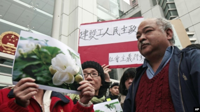 "Protesters hold up pictures of jasmine flowers during a ""Jasmine Revolution"" protest outside the Chinese liaison office in Hong Kong February 20, 2011."