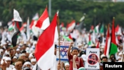 Protesters hold signs during a rally to condemn U.S. President Donald Trumps's decision to recognize Jerusalem as Israel's capital, at Monas, the national monument, in Jakarta, Indonesia, Dec. 17, 2017.