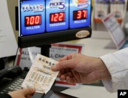 A customer is handed a Powerball ticket in Omaha, Neb., Aug. 23, 2017. Lottery officials said the grand prize for Wednesday night's drawing has reached $700 million. The second-largest on record for any U.S. lottery game.