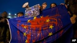 People hold an European Union flag stained with red paint as they protest against the possible deal between the EU and Turkey to return thousands of migrants, in Madrid, Spain.