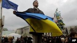 Seorang demonstran anti-pemerintah Yanukovych memegang bendera Ukraina di Lapangan Merdeka, Kyiv, Ukraina (25/2).