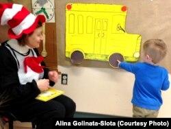 Бібліотекарка, перевдягнена в костюм книжкового героя, запитує дитину, якої форми колеса в автобуса