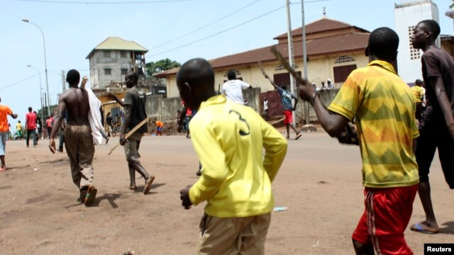 FIILE - Opposition protesters carry sticks as they march along a street in Conakry, May 2013.