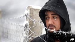 A migrant stands next to a fence during snowfall at the Lipa camp, outside Bihac, Bosnia. A fresh spate of very cold winter weather on has brought more misery for hundreds of migrants who have been stuck for days in a burnt-out camp.