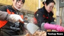 3일 청주시 상당구 서문시장 삼겹살거리에서 열린 '삼겹살데이 무료시식회'에 참여한 자원봉사자들이 삼겹살을 굽고 있다.