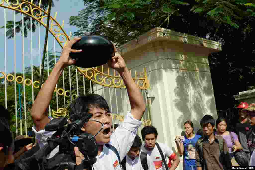 A demonstrator in front of Yangon University holds a monk's bowl upside down, a symbol of opposition.