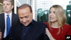 Silvio Berlusconi, président de l'AC Milan, accompagné de sa fille Barbara, signe des autographes pour des supporters au quartier général de son club, à Milan, Italie, 3 juillet 2015.