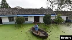 在安徽合肥,有人在被水淹了的房子附近划船(2016年7月9日)