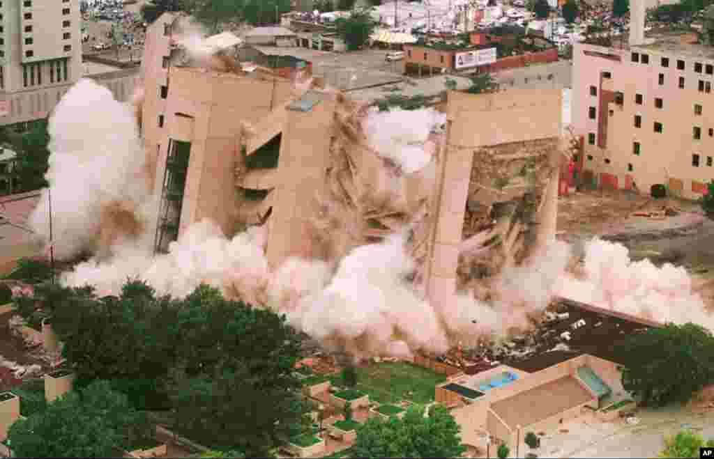 FILE - In this May 23, 1995 file photo, the Alfred P. Murrah Federal Building in downtown Oklahoma City falls in a cloud of dust as it was demolished by exposives. The building was the site of a deadly car-bomb attack April 19, 1995.