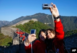 Miss World contestants Kamilla Salgado of Brazil, right, and Tang Xiao of China take a photo of themselves while visiting the Mutianyu Great Wall in Beijing, China Tuesday, Oct. 5, 2010.