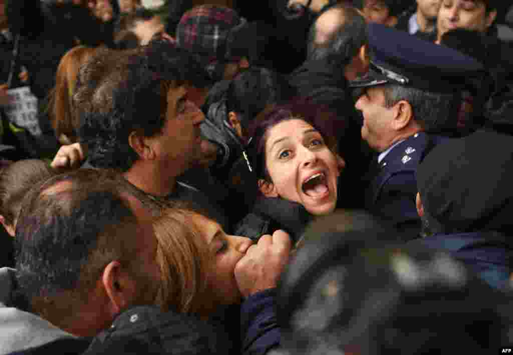 A Cyprus Airways employee shouts as she is pushed against a police line at the Ministry of Finance in Nicosia during a protest against the closing down of Cyprus Airways.