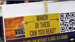 GMO Labeling: A sign hangs at a rally Friday July 1, 2016 in Montpelier, Vt., protesting a proposal by Congress that would allow companies to use computer labels to indicated whether a product has been made with the help of genetic engineering.