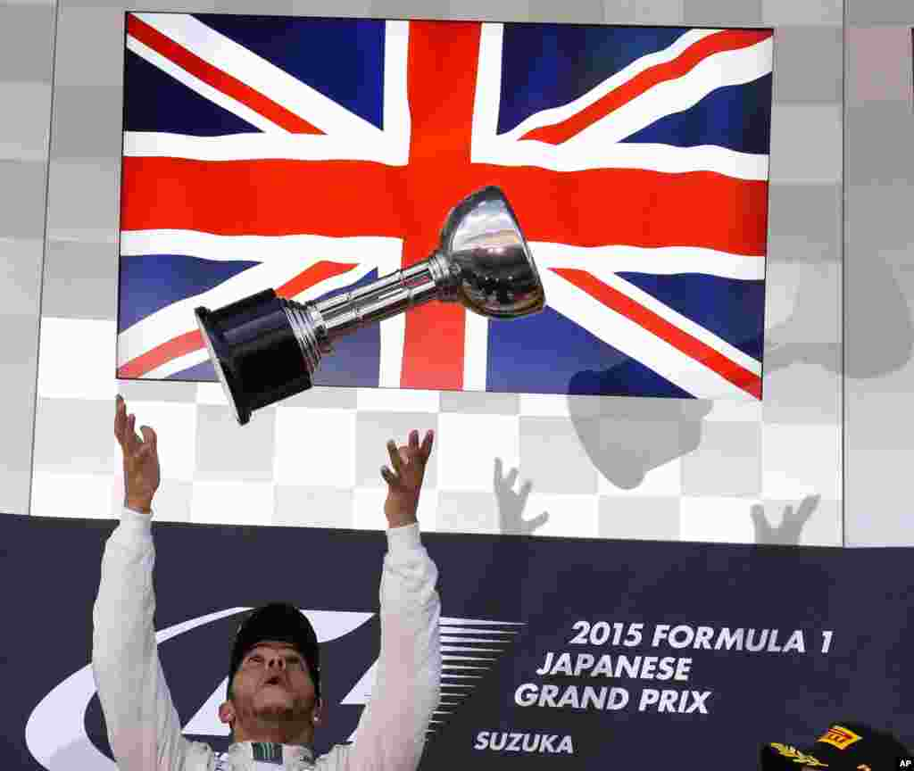 Mercedes driver Lewis Hamilton of Britain throws the trophy into the air on the podium after winning the Japanese Formula One Grand Prix at the Suzuka Circuit in Suzuka, central Japan.