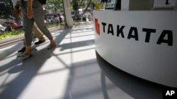 FILE - Visitors walk by a Takata Corp. desk at an automaker's showroom in Tokyo. One type of Takata air bag inflator can explode with too much force.