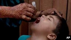 Un trabajador de salud vacuna a un niño contra la polio durante una campaña en Karachi, Paquistán. 25-7-16.