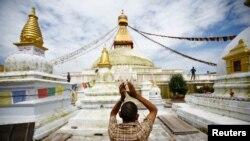 Seorang pria Budha tengah beribadah di dekat stupa Boudhanath di Kathmandu (6/8). Seorang warga Tibet dilaporkan tewas setelah melakukan aksi bakar diri di dekat stupa ini, Selasa pagi waktu setempat.