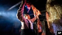 Cory Williams, 17, hangs moose intestines in the smokehouse of the Stevens family hunting camp, September 15, 2021, near Stevens Village, Alaska.