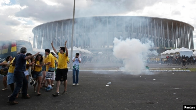 Soccer fans walk away from a cloud of tear gas as riot police clash with demonstrators outside the Mane Garrincha National Stadium in Brasilia, June 15, 2013.