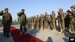 FILE - General Sher Mohammad Karimi, chief of staff of the Afghan army, second left, salutes soldiers during a ceremony in Laghman province, east of Kabul, Afghanistan, Jan. 11, 2015.