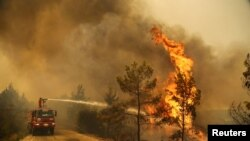 Seorang petugas memadamkan kebakaran hutan di dekat kota Manavgat, sebelah timur kota resor Antalya, Turki, 30 Juli 2021. (Foto: REUTERS/Kaan Soyturk)
