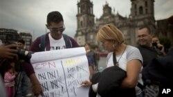 Seorang karyawan situs berita Meksiko menyelenggarakan jajak pendapat pemilu presiden untuk mencari siapa yang terunggul antara capres Andres Manuel Lopez Obrador (kanan) dan Enrique Pena Nieto, di Lapangan Zocalo di Mexico (29/6).