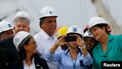 Brazil's president, Dilma Rousseff, prepares to take a photo with workers as IOC Coordination Commission head Nawal El Moutawakel (bottom L) watches during a visit to the Rio 2016 Olympic Park in Rio de Janeiro September 30, 2014.