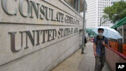 A man wearing a mask to protect himself from catching a deadly pneumonia-like virus walks past the US consulate.