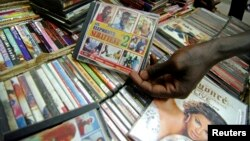 A shopper holds a pirated copy of a TV sitcom in downtown Ouagadougou, March 2, 2009.