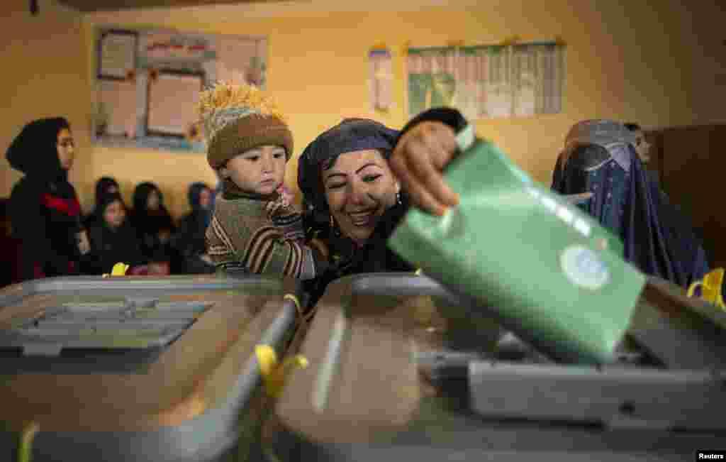 زنی کودک به بغل رأیش را در صندوق می اندازد - مزار شریف، ۵ آوریل ۲۰۱۴