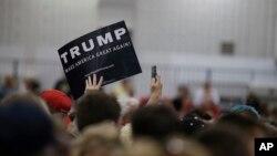Seorang pendukung Donald Trump melambaikan papan bertuliskan nama kandidat calon presiden Partai Republik itu dalam kampanye di Indianapolis, Indiana (20/4). (AP/Darron Cummings)