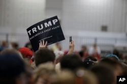 A supporter for Republican presidential candidate Donald Trump holds up a sign during a campaign stop, April 20, 2016, in Indianapolis, Indiana.