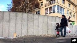 Місцеві жителі йдуть біля стіни побудованої сербською етнічною меншиною в місті Митровиця