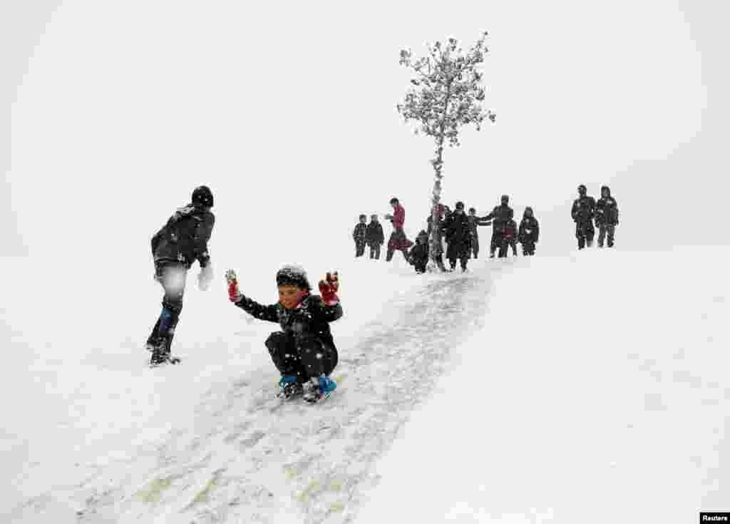 Afghan boys slide down a snow-covered slope in Kabul.