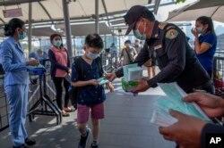戴着防护口罩的泰国卫生官员在曼谷的一个商场里发放口罩。(2020年1月28日)