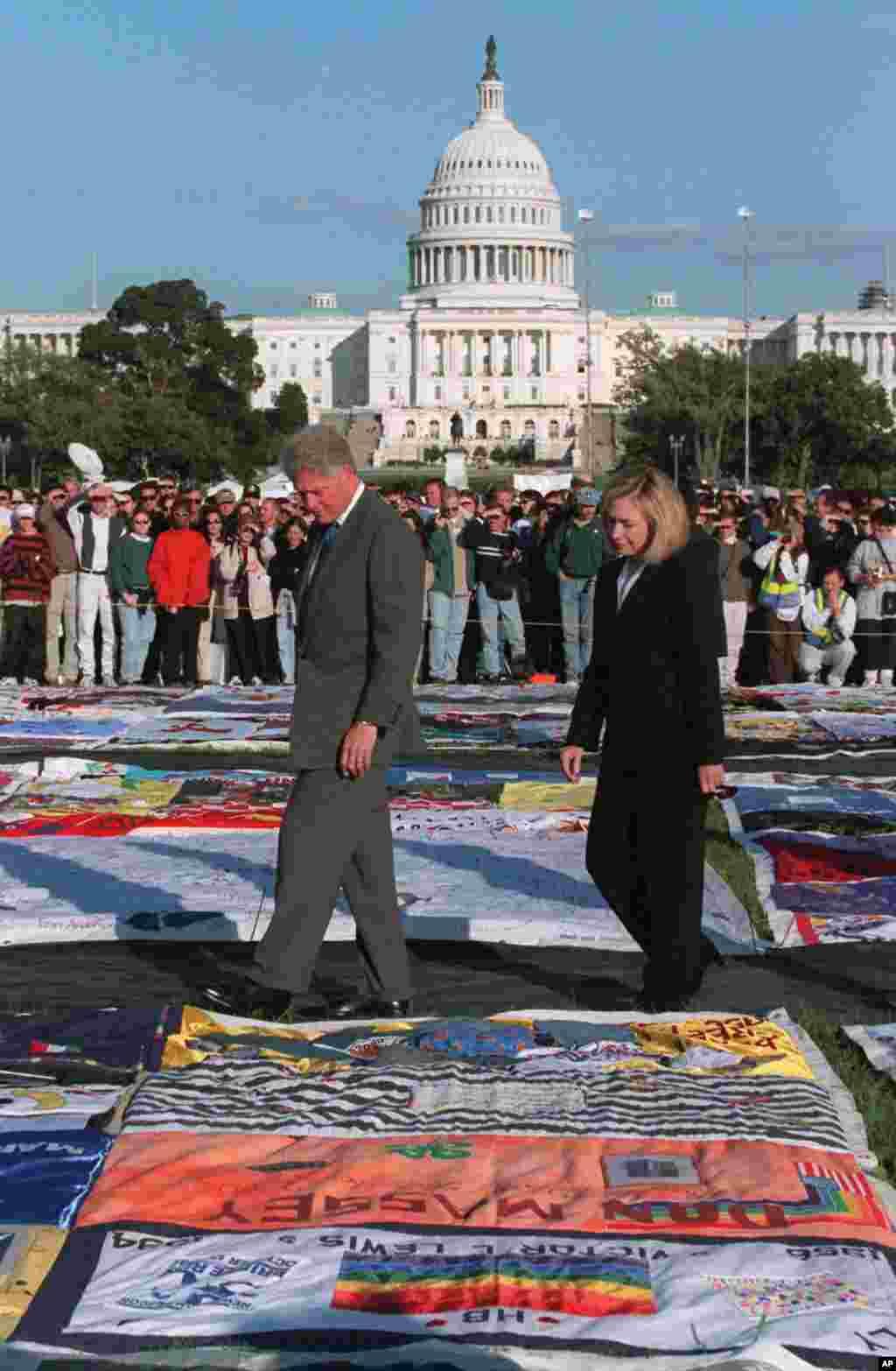 """En presidente de entonces, en 1996, Bill Clinton y su esposa, caminan en la Alameda Nacional a lo largo de """"El edredón del VIH""""."""