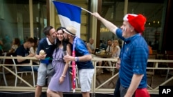 France fans pose for photo with a Russian woman in Nikolskaya street near Red Square in eve of the final soccer match Croatia and France during the 2018 soccer World Cup in Moscow, Russia, Saturday, July 14, 2018.