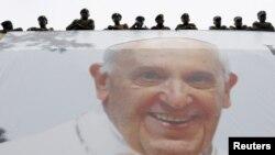 Du dessus d'une affiche au visage du pape François, des officiers de l'armée kényane assistent à une messe qu'il célèbre à Nairobi, au Kenya, le 26 novembre 2015. (Photo REUTERS/Stefano Rellandini)