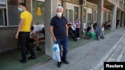 ARHIVA - Ljudi koji sumnjaju da su zaraženi koronavirusom čekaju ispred ulaza u Kliniku za tropske i infektivne bolesti Kliničkog centa Srbije, 26. juna 2020. (Rojters, Marko Đurica).