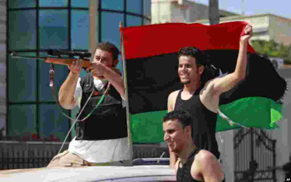 Libyan rebel fighters celebrate as they drive through Tripoli's Qarqarsh district. Libyan government tanks and snipers put up scattered, last-ditch resistance in Tripoli on Monday after rebels swept into the heart of the capital, Aug. 22, 2011 (Reuters)