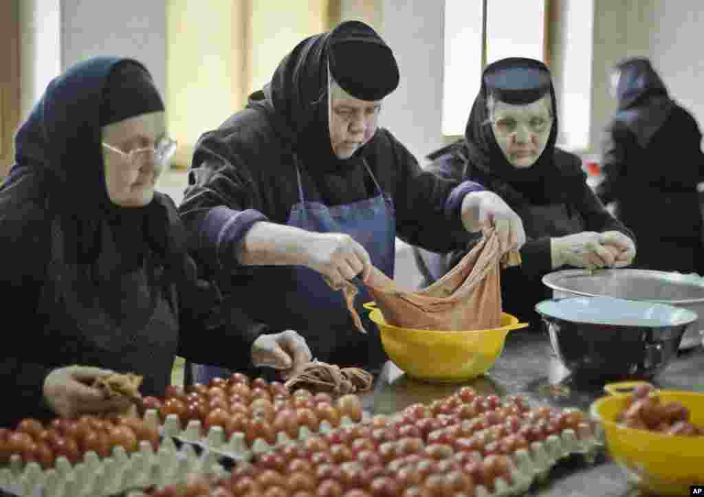 An Orthodox nun handles colored eggs at the Timiseni Monastery, outside Sag, western Romania, April 18, 2014.