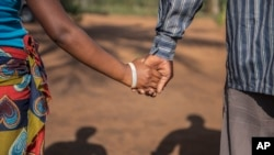 A 15-year-old pregnant girl holds hands with her 20-year-old husband-to-be in Mozambique, Nov. 18, 2015. (AP)