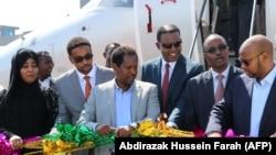 Abdirahman Omar Osman (3ème à gauche) et Abera Lemi (3ème à droite), PDG d'Éthiopienne National Airways, inaugurent après le premier vol commercial de National Airways reliant Addis-Abeba à Mogadiscio.