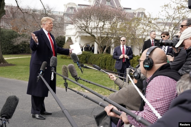 President Donald Trump talks to reporters as he departs on travel to Ohio from the White House in Washington