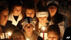 Pennsylvania State University students hold candles during a vigil to show their support for sexual abuse victims involved in the recent controversy at their school, November 11, 2011.