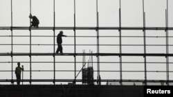 Laborers work on scaffolding at a residential construction site in Hefei, Anhui province, China.