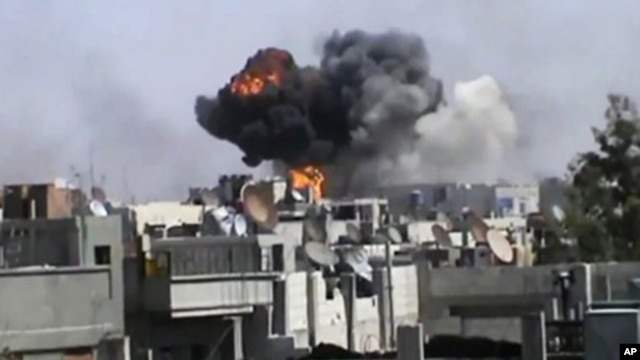 Smoke billows an impact following purported shelling in Khaldiyeh district, Homs, Syria. (file)