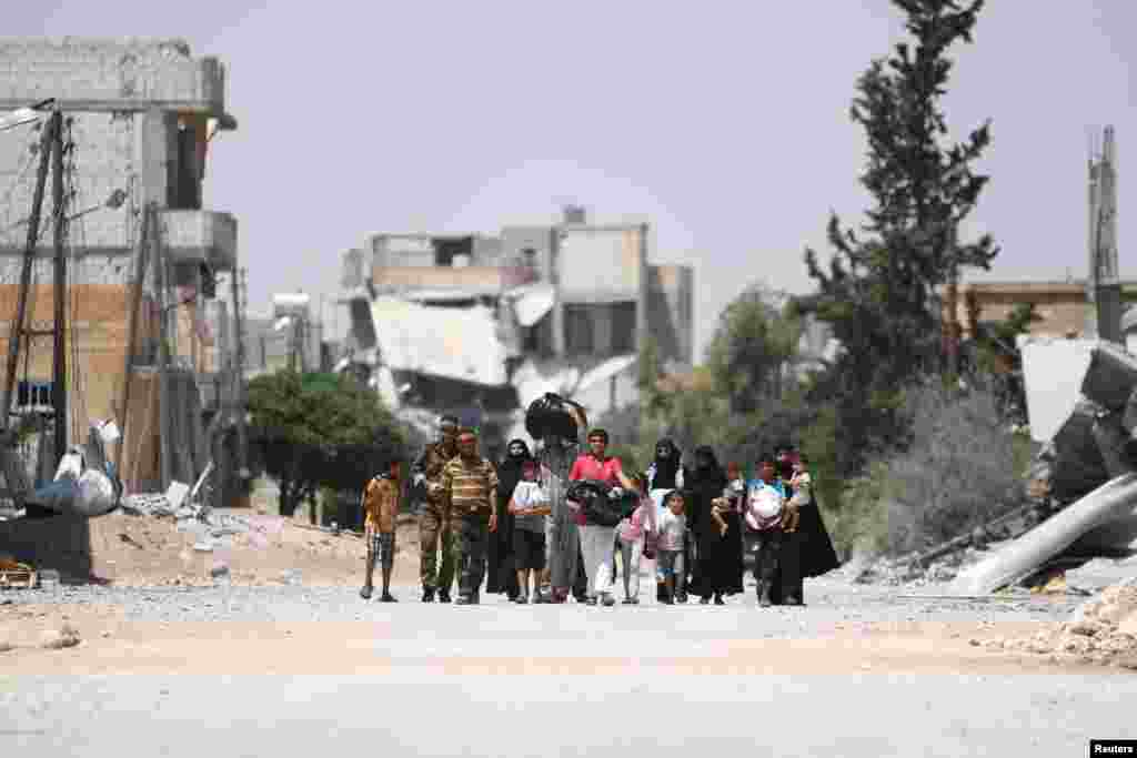 Syria Democratic Forces (SDF) fighters walk with people whot fled their homes due to clashes between Islamic State fighters and SDF in Manbij, in Aleppo Governorate.